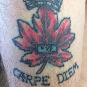 Un gros plan d'un tatouage d'une feuille d'érable et des mots