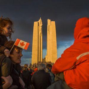 Deux enfants sont assis au-dessus des épaules des adultes. Le monument commémoratif Vimy, éclairés par le soleil, en arrière-plan.