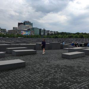 Une fille se promène dans un champ de gros blocs de pierre grise.