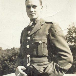 Une photographie en noir et blanc d'un homme en uniforme tenant une cigarette et regardant la caméra