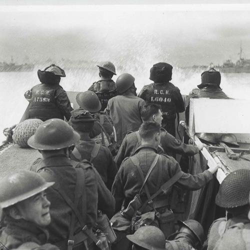 Un groupe de soldats canadiens portants des casques Mark II sur une péniche de débarquement.