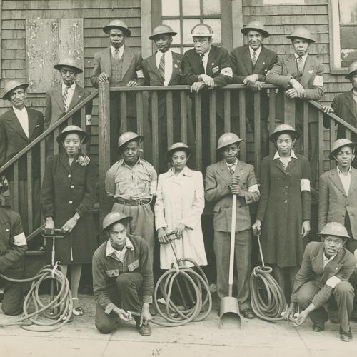 Un groupe de bénévoles afro-canadiens, hommes et femmes, pose avec des casques Mark II et des boyaux.