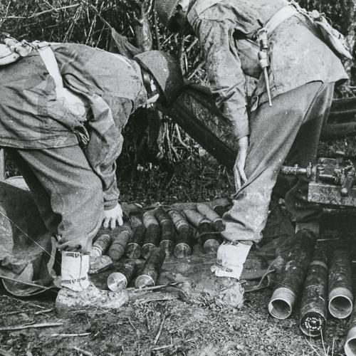 Deux soldats se penchent en empilant des munitions.