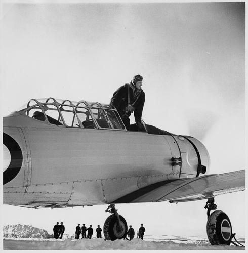 Un pilote se tient dans le cockpit, regardant par-dessus l'aile d'un l'avion
