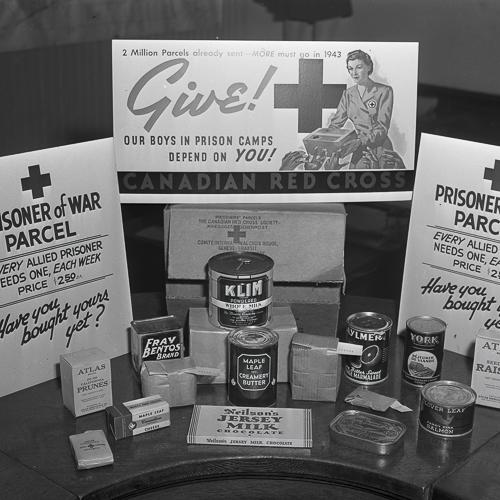 Un colis de la Croix-Rouge déballé pour montrer la nourriture en conserves et un savon de la Croix-Rouge.
