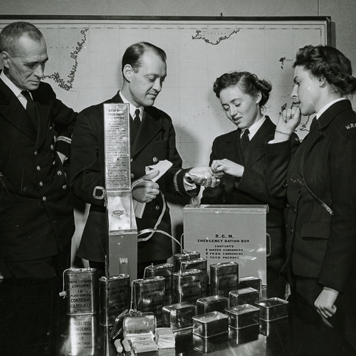 Deux hommes et deux femmes de la marine, déballent et dégustent la ration de chocolat d'un boîte de rationnement.