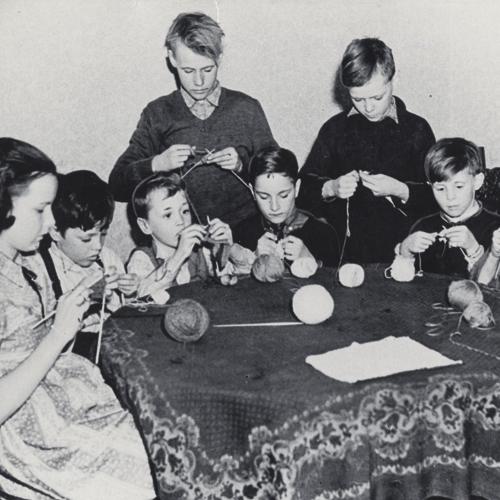 Huit garçons et une fille assis autour d'une table tricotant.