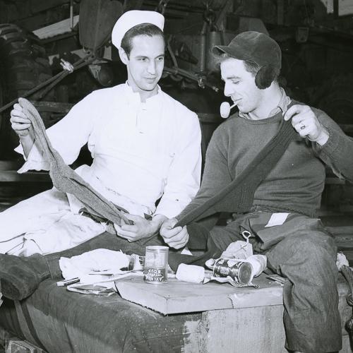 Deux marins assis ensemble tiennent en place deux chaussettes tricotées à la main.