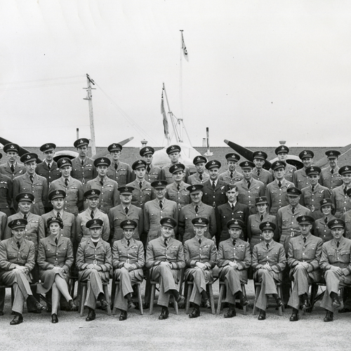 Soixante officiers en rangées posent pour un portrait de groupe. Le groupe comprend trois femmes.