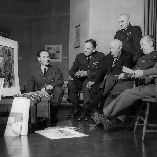 Sept hommes sont assemblés autours de plusieurs œuvres terminées, en discutant.
