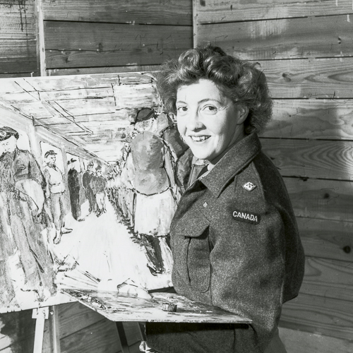 Molly Lamb Bobak, dans son atelier. En uniforme, elle se tient devant une peinture sur un chevalet en tenant une palette.