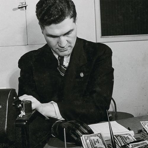 Un homme en tailleur compte de l'argent sur son bureau. Sa main droite prothétique repose sur le bureau devant lui.
