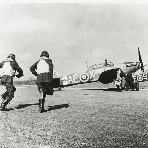 Deux pilotes de chasse de l'ARC courant vers deux avions Hawker Hurricane sur un terrain d'aviation.