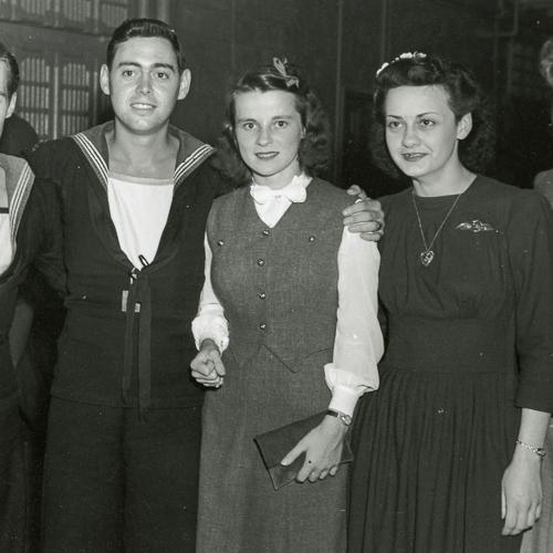 Deux marins en uniforme posent avec trois jeunes femmes civiles.