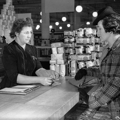 Une femme achète de la nourriture avec des coupons de rationnement d'une employée.
