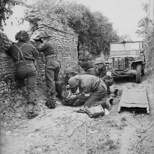 Trois soldats soignent un soldat blessé. Trois autres soldats défendent la position, se tenant derrière un mur de pierre.