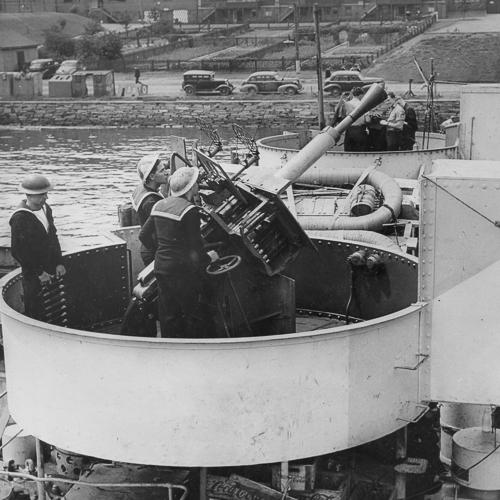 Trois marins à côté d'un canon antiaérien sur un navire.