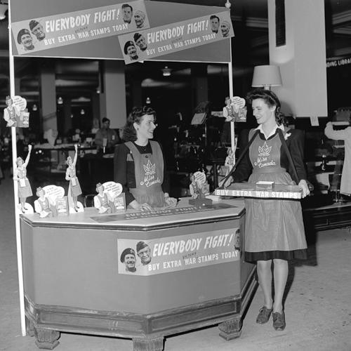 Deux femmes portant un tablier Miss Canada à un kiosque de vente de timbres d'épargne de guerre.