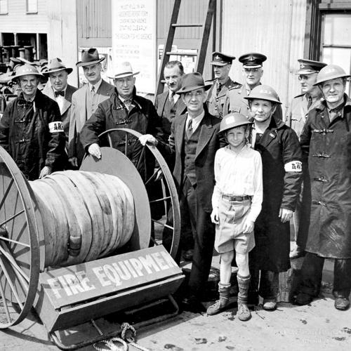 Des ouvriers de chantier naval et un jeune garçon posent à côté d'un tuyau d'incendie.