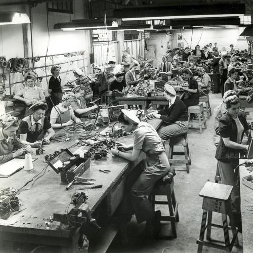 Quelques femmes sur les planchers d'une usine, portent un fichu et d'autres, un chapeau.
