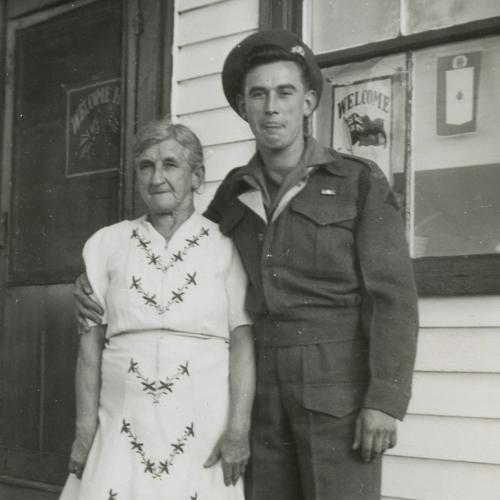 Le soldat et sa mère à l'extérieur de leur maison.