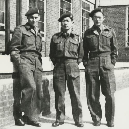 Trois professeurs de langue Canadiens japonais en uniformes de l'armée devant leur école.