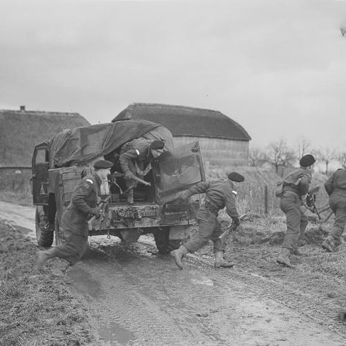 Des soldats sautent d'un camion blindé.