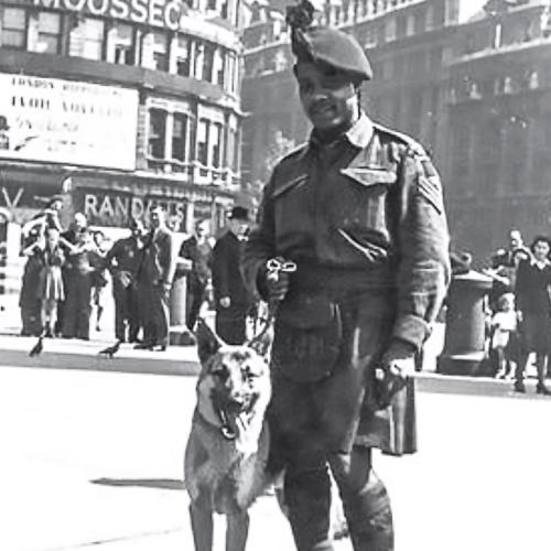 Un soldat afro-canadien portant sa veste de tenue de combat et un kilt pose avec son chien sur une rue à Londres.