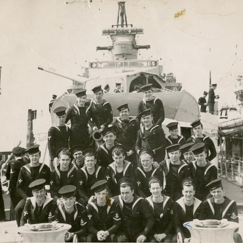 Un groupe de marins pose à bord leur navire portant leurs casquettes à différents angles.