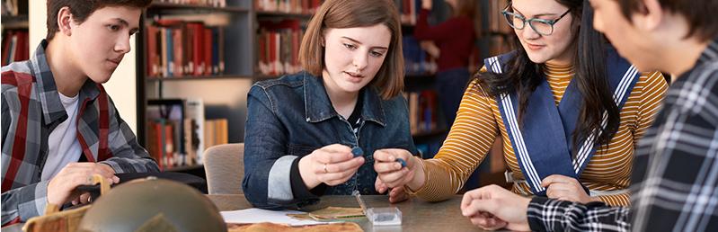 Des élèves examinent des artefacts de la Boite de découverte sur la Deuxième guerre mondiale.