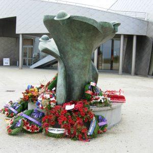 Une statue commémorative stylée avec des couronnes, des fleurs et des coquelicots posés à sa base ...