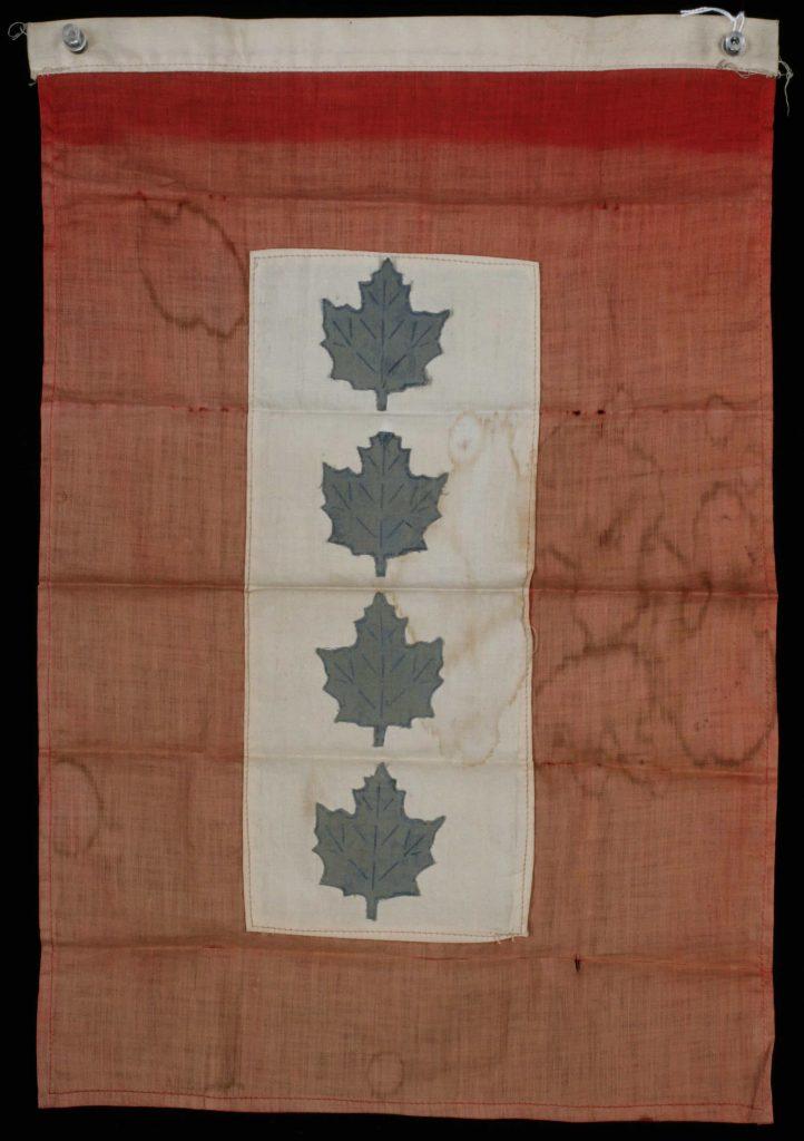 Drapeau rouge délavé avec, en son centre, un écusson blanc orné de quatre feuilles d'érable bleues