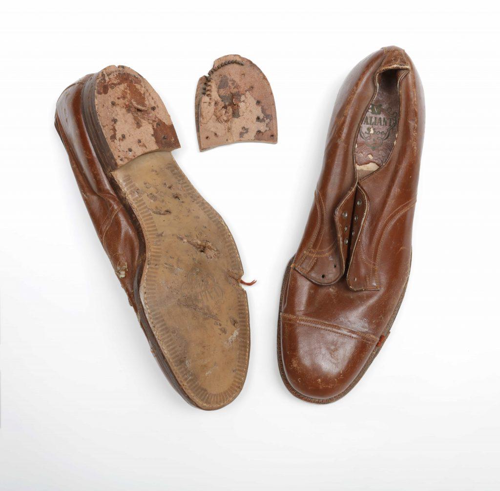 Deux chaussures en cuir marron, dont l'une est à l'envers, montrant une semelle endommagée et un talon détaché.
