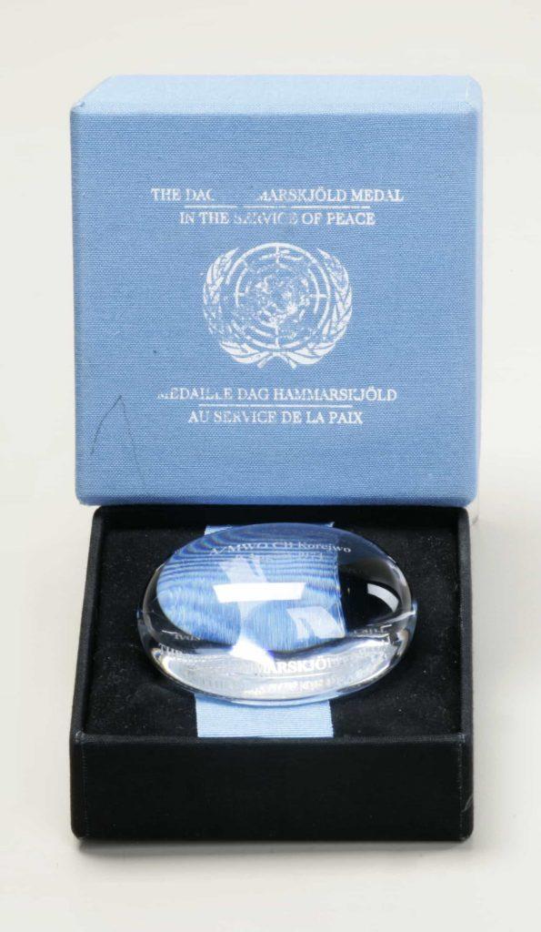 Objet en cristal clair en forme de sphère légèrement aplatie, orné d'une gravure, dans un écrin portant la mention «The Dag Hammarskjöld Medal/In the Service of Peace/Médaille Dag Hammarskjöld/Au service de la paix» sur le couvercle.