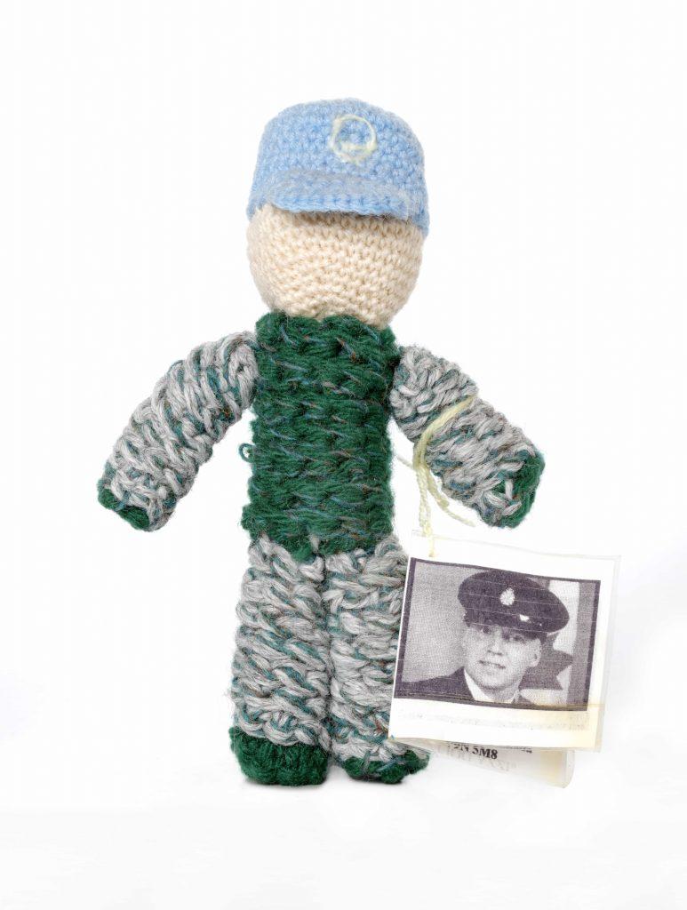 Poupée tricotée portant un béret bleu clair et des vêtements verts de style camouflage. À son bras est fixée une étiquette montrant le visage d'un homme en uniforme.