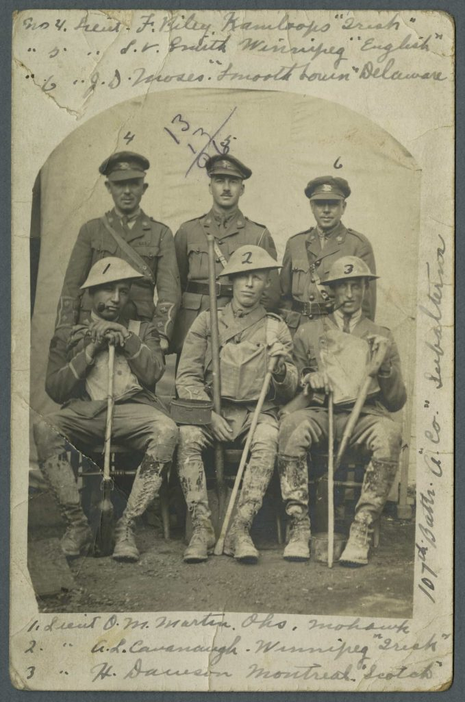 Trois hommes en uniforme se tiennent derrière trois autres assis, aux uniformes tachés de boue et tenant des pelles et des bâtons de marche. Tous sont identifiés par des numéros et un court texte.