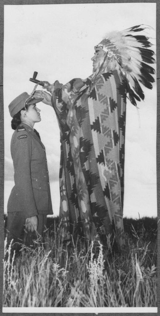 Une femme autochtone en uniforme est agenouillée dans un champ, devant un Autochtone dont les vêtements et les objets de cérémonie sont mal assortis.