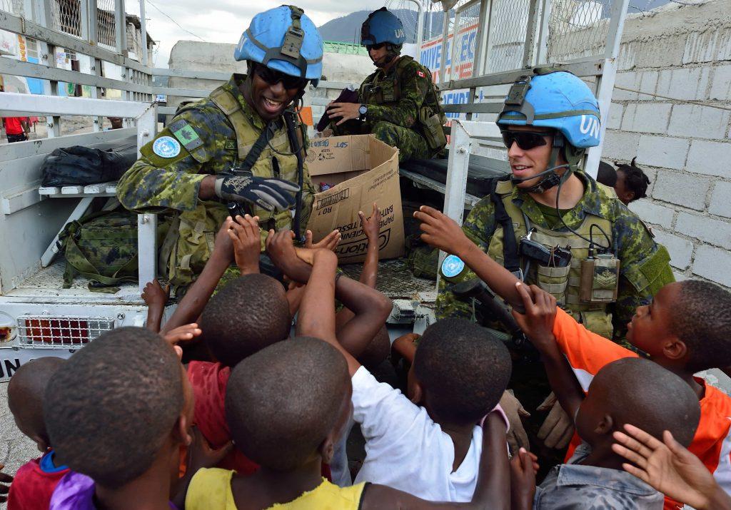 De nombreux enfants noirs entourent un homme noir souriant en uniforme (Casque bleu), sous le regard d'un homme blanc également en uniforme de maintien de la paix.