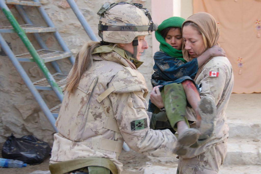 Une femme en uniforme porte une enfant afghane dans ses bras, assistée par une autre femme en uniforme.