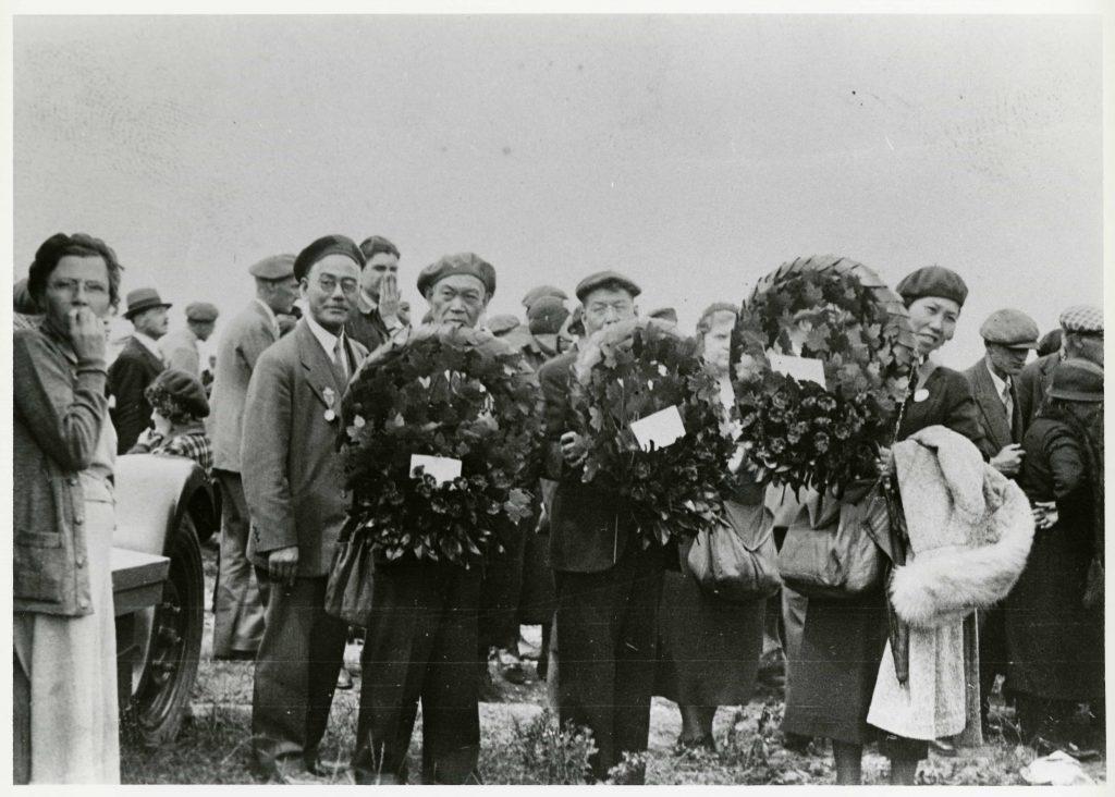 Dans une foule, trois Canadiens et une Canadienne, tous d'origine japonaise, tiennent des couronnes et regardent le photographe.