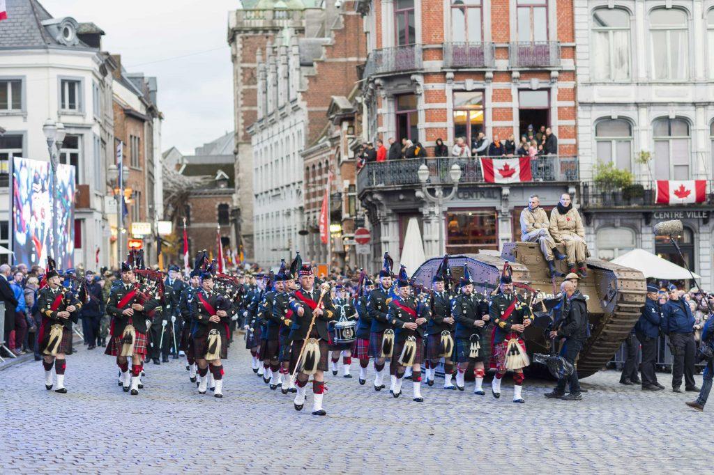 Des hommes portant des uniformes de cérémonie défilent dans une rue de Mons, le long de bâtiments décorés de drapeaux canadiens. Deux hommes sont assis sur un char d'assaut de l'époque de la Première Guerre mondiale.