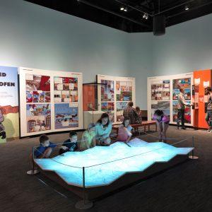 Enfants et adultes coopérant avec un interactif dans l'exposition