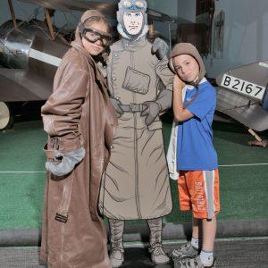 Deux enfants se déguisent en tant que pilotes et posent avec une découpe d'un pilote de bande dessinée.
