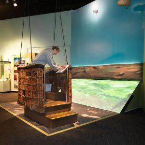 Un jeune homme en interaction avec un interactif dans l'exposition