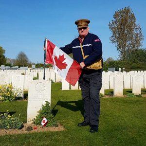Un homme avec un drapeau canadien dans un cimetière